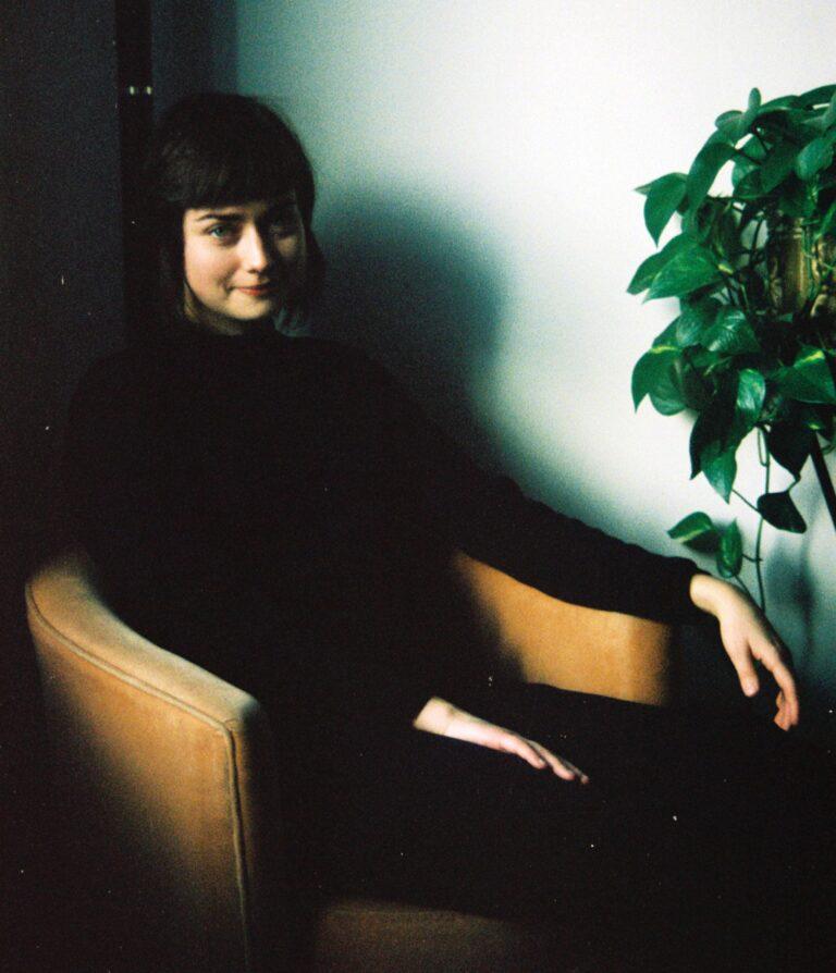 Deidre Morrison is sitting in an armchair beside a plant.