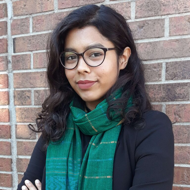 Headshot of Najeeba Ahmed, portrait style, positioned in front of a red brick wall.