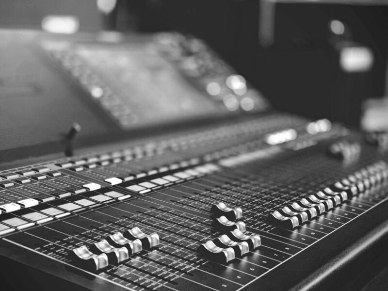A moody black and white photo of an expensive looking mixing board.