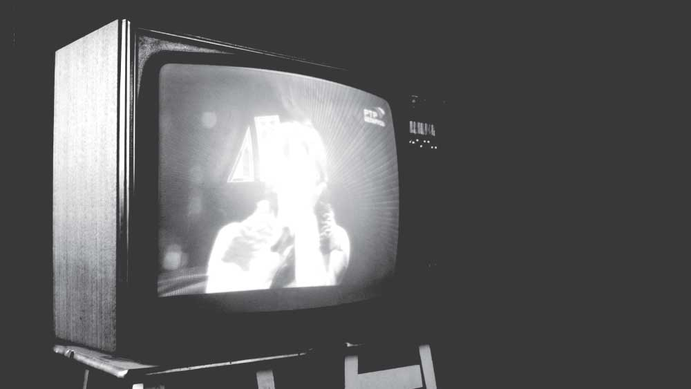 An old picture-tube tv in the dark, glowing with noise and blurred images.