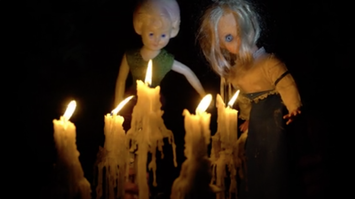 Two dolls watching candles burn and drip wax.
