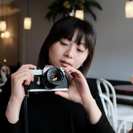 A photo of Yan holding a camera.
