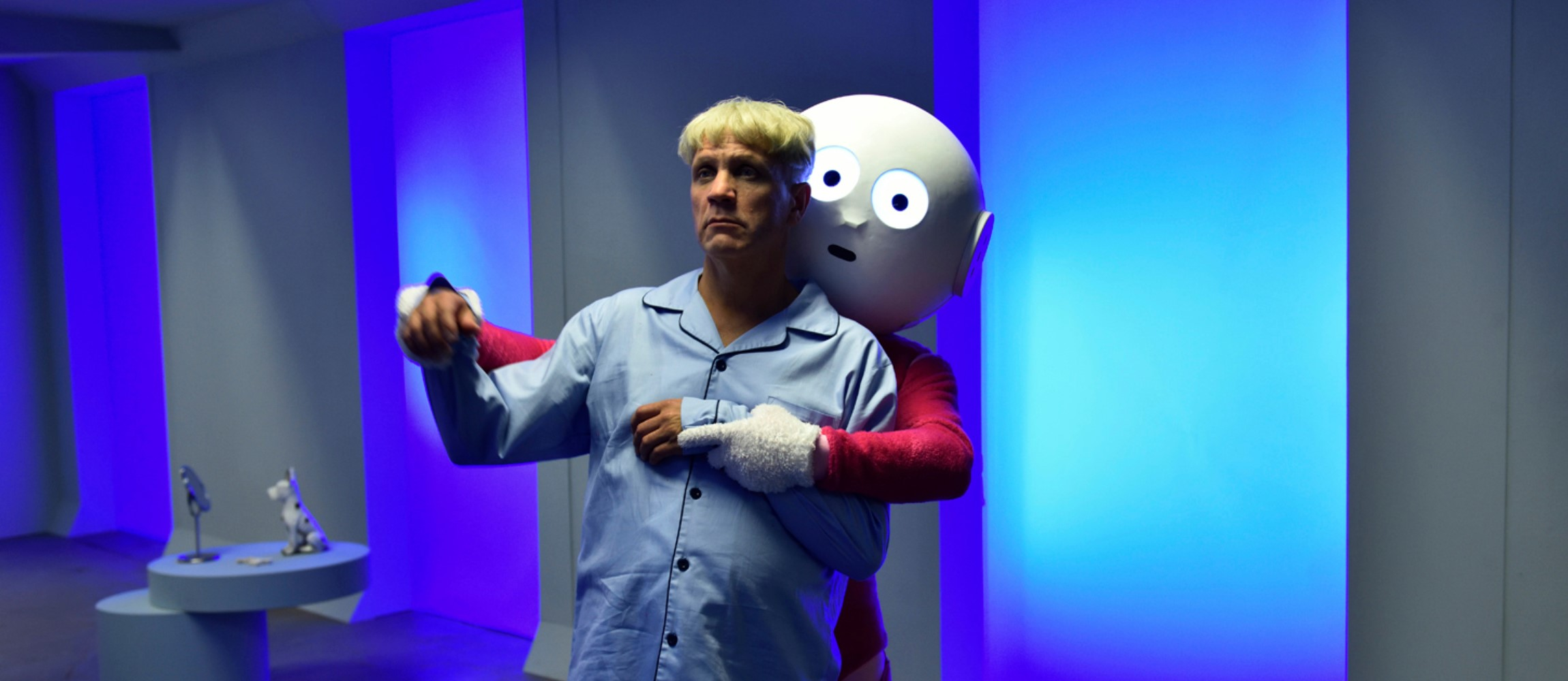 A man is held by a large doll with wide eyes. The room they inhabit is blue and modern.